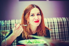 Young woman is eating mixed vegetable salad in cafe and drinks wine Stock Images