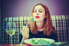 Young woman is eating mixed vegetable salad in cafe and drinks wine Royalty Free Stock Image