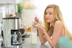 Young woman eating muesli in kitchen Stock Photography