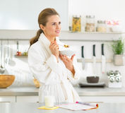 Young woman eating muesli in kitchen Stock Image