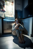 Young woman eating next to refrigerator at night Royalty Free Stock Image