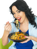 Young Woman Eating Noodles with Stir Fried Vegetables Stock Images