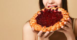 Young woman eating open pie with a stuffing stock image