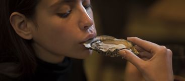 Young woman eating oyster in luxury restaurant. Face girl for magazine cover. Girl face portrait in your advertisnent. Stock Image