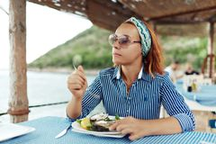Young woman eating oyster in an outdoor restaurant stock photo