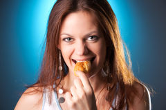 Young woman eating patty portrait Stock Images