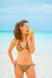 Young woman eating pear on beach Royalty Free Stock Photography
