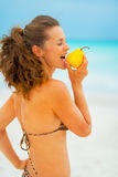 Young woman eating pear on beach Stock Image