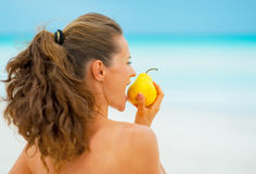 Young woman eating pear on beach Royalty Free Stock Photos