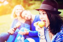 Young woman eating a pear and having picnic with friends royalty free stock photos
