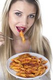 Young Woman Eating Penne Pasta. Model Released. Attractive Young Woman Eating Penne Pasta Royalty Free Stock Images