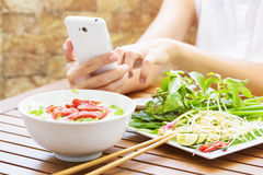 Young woman eating the Pho Bo and using a smartphone in Vietnam Royalty Free Stock Image