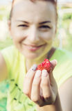 Young woman eating piece of fresh strawberry Royalty Free Stock Photo