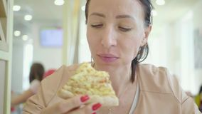 A young woman is eating a piece of pizza. Charming happy girl laugh and biting off big slice of fresh made pizza stock video