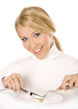 Young Woman Eating a Pill. Portrait of smiling girl with fork and knife eating a pill Royalty Free Stock Photo