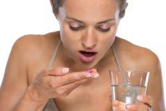 Young woman eating pills Royalty Free Stock Photos