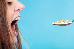 Young woman eating pills on a spoon Royalty Free Stock Photo