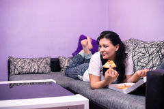 Young woman is eating pizza in livving room. Young woman is eating vegetarian pizza in livving room Royalty Free Stock Photos