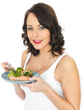 Young Woman Eating Poached Salmon and Vegetables Stock Photos