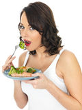 Young Woman Eating Poached Salmon and Vegetables Stock Images