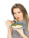 Young Woman Eating Poached Slamon and Salad Royalty Free Stock Images