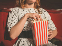 Young woman eating popcorn in movie theater Stock Image