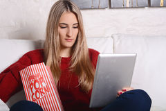 Young woman eating popcorn and watching movies on tablet. Stock Photos