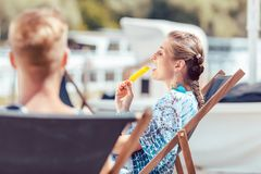 Young woman eating popsicle. Young women sitting on chair eating popsicle royalty free stock photography