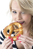Young Woman Eating a Pretzel Stock Image