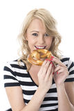 Young Woman Eating a Pretzel Stock Photography