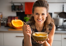 Young woman eating pumpkin soup in kitchen. Happy young woman eating pumpkin soup in kitchen Royalty Free Stock Photo