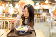 Young Woman eating ramen in restaurant Stock Photo