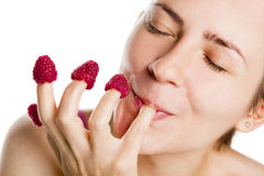 Young woman eating raspberries from fingers. Stock Images