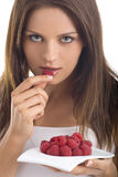 Young woman eating raspberry.  royalty free stock photos