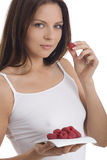 Young woman eating raspberry.  stock photo