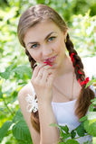 Young woman eating raspberry in garden Royalty Free Stock Photography