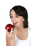 Young woman eating red apple. Young woman looking at red apple as she's getting ready to eat it Royalty Free Stock Photo
