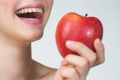 Young woman eating red apple Stock Images