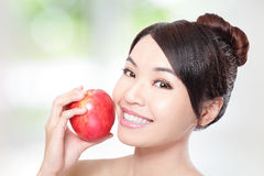 Young woman eating red apple with health teeth. Beautiful young woman eating red apple with health teeth. Isolated over green background, asian beauty model Stock Photography