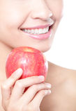 Young woman eating red apple with health teeth Stock Photography