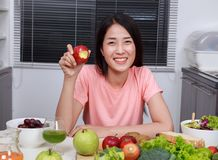 Young woman eating apple in kitchen royalty free stock photo