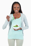 Young woman eating salad. Against a white background Stock Photo