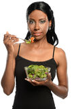Young Woman Eating Salad. Young African American woman eating salad isolated over white background Stock Images