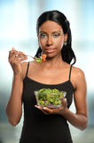 Young Woman Eating Salad. Young African American woman eating salad with large window in background Royalty Free Stock Photography