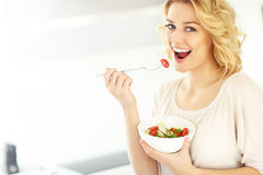 Young woman eating salad in the kitchen Royalty Free Stock Photography