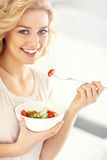 Young woman eating salad in the kitchen Stock Photography