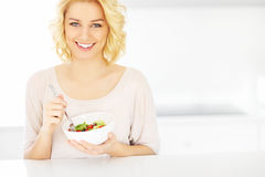 Young woman eating salad in the kitchen Stock Images