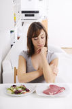 Young woman eating salad and meat. Concept of choosing Stock Photo