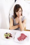 Young woman eating salad and meat. Smiling and looking in camera Stock Image