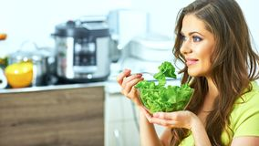 Young woman eating salad sitting in kitchen Royalty Free Stock Images